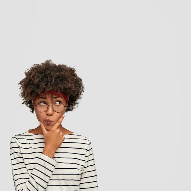 Verticale shot van verwarde aarzelende vrouw houdt kin vast en tuitt lippen, kijkt vol ongeloof naar boven, houdt kin vast Gratis Foto