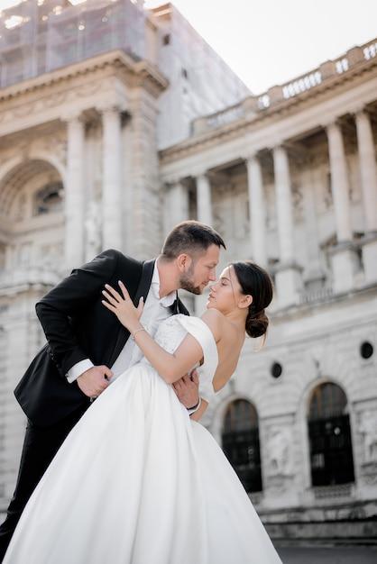 Verticale trouwfoto van bruid en bruidegom een moment voor een kus voor historisch gebouw Gratis Foto