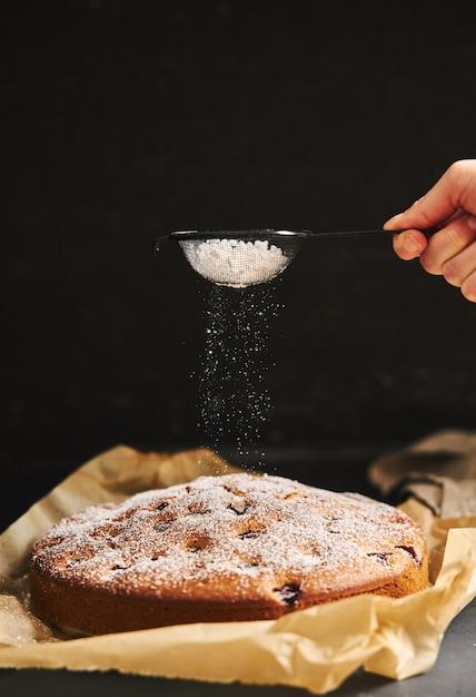 Verticale weergave van een cherry cake met suikerpoeder en ingrediënten aan de zijkant op een zwarte achtergrond Gratis Foto