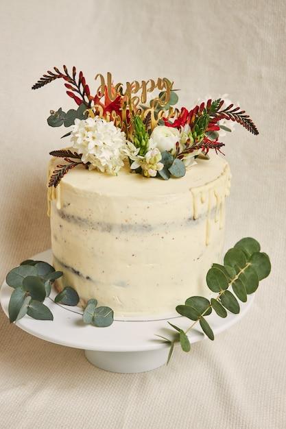 Verticale weergave van een heerlijke verjaardag crème witte bloemen op de bovenste taart met een infuus aan de zijkant Gratis Foto