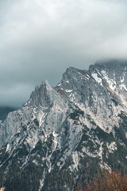 Verticale weergave van een hoge berg onder de bewolkte hemel Gratis Foto