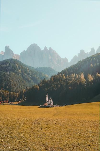 Verticale weergave van een prachtig gebouw op een droog grasveld omgeven door beboste bergen Gratis Foto