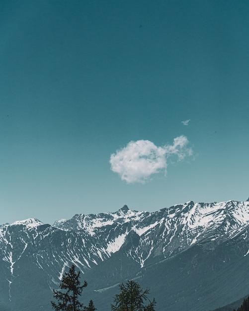 Verticale weergave van een schattige kleine wolk met de achtergrond van bergen en blauwe lucht Gratis Foto