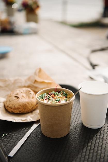 Verticale weergave van een tafel met een kopje koffie salade en brood op een onscherpe achtergrond Gratis Foto