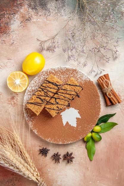 Verticale weergave van smakelijke desserts versierd met chocoladesiroop en citroen op kleurrijke tafel Gratis Foto