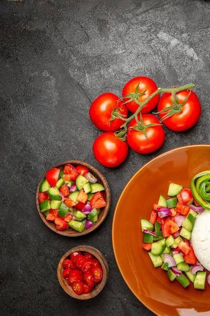 Verticale weergave van veganistisch diner met rijst en verschillende soorten groenten op zwarte tafel Gratis Foto