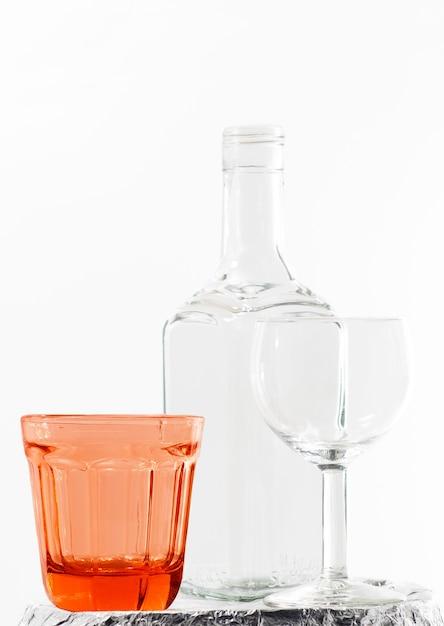 Verticals heet van een lege fles en glazen op witte achtergrond Gratis Foto