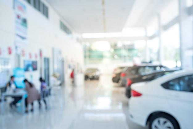 Vervaag de achtergrond van de auto en de showroom op wazig op de werkplek of abstracte achtergrond van ondiepe kantoor diepte van focus. Premium Foto