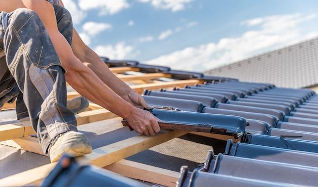 Vervaardiging van het dak van een gezinswoning uit keramische tegels. kopieer ruimte Premium Foto