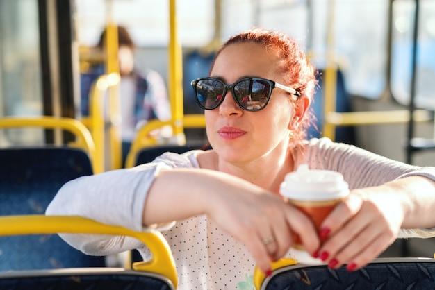 Verveeld blanke vrouw van middelbare leeftijd zitten in de stadsbus, leunend op de stoel en het drinken van koffie te gaan. Premium Foto