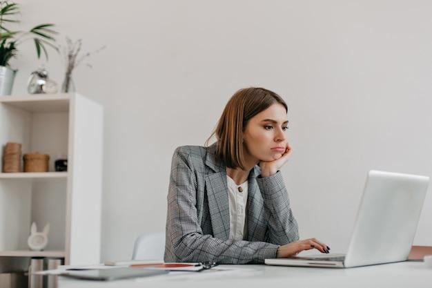 Verveeld jonge zakelijke dame in grijze outfit kijkt laptop scherm op haar werkplek. Gratis Foto