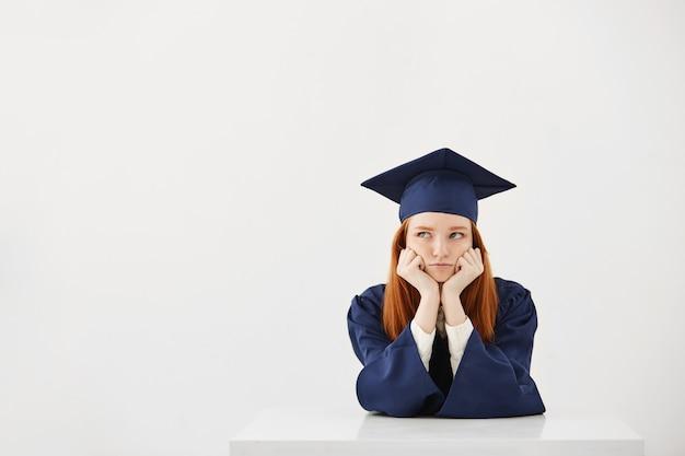 Verveeld vermoeide vrouwelijke afgestudeerde denken zittend op witte backround exemplaar ruimte. Gratis Foto