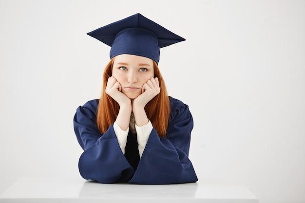 Verveeld vermoeide vrouwelijke afgestudeerde denken zittend op witte backround. Gratis Foto