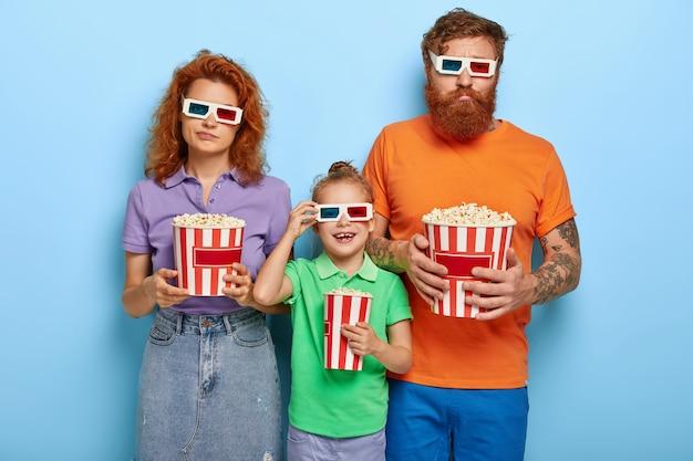 Verveelde mama en papa die onverschillig zijn terwijl hun dochter naar interessante tekenfilms in de bioscoop kijkt, een driedimensionale bril draagt, lichte casual zomerkleding, vrije tijd doorbrengt voor entertainment Gratis Foto