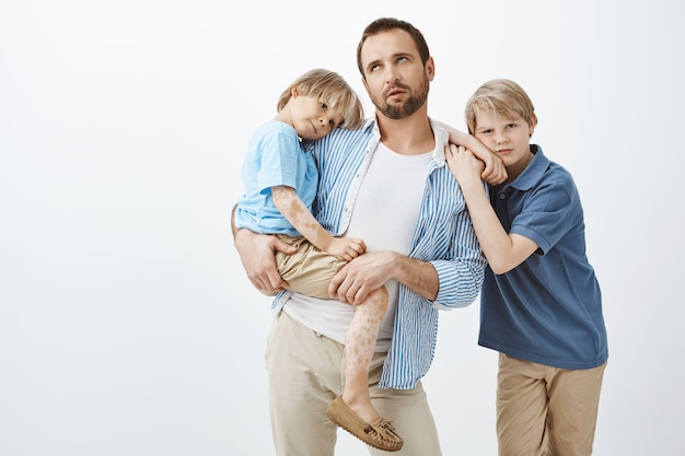 Verveelde sceptische europese vader in casual outfit met klein kind met vitiligo, rollende oogleden van ergernis of vermoeidheid Gratis Foto