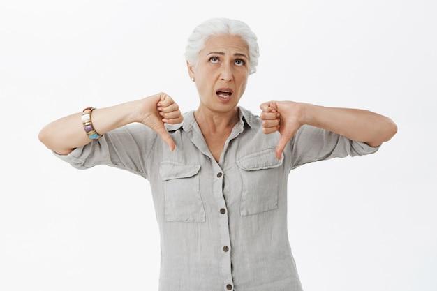 Verveelde sceptische oudere vrouw die ontevreden kijkt, duimen naar beneden toont in afkeer en ogen oprolt Gratis Foto