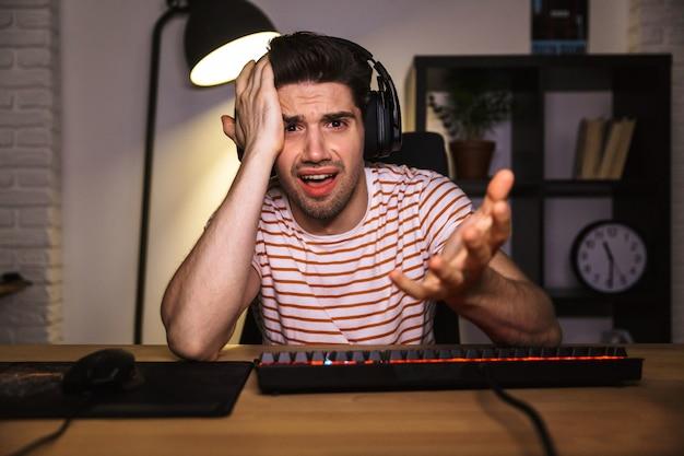 Verward gamer spelen van videogames op computer Premium Foto