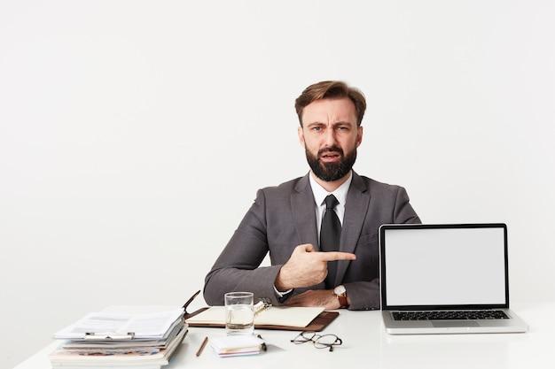 Verward jonge knappe brunette man met baard en kort kapsel poseren over witte muur aan werktafel en tonen met wijsvinger op zijn laptop Gratis Foto