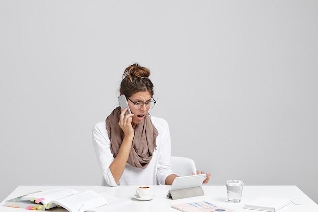 Verward vrouwelijke kantoormedewerker heeft wat problemen met werken op tablet, monteur belt, probeert probleem op te lossen Gratis Foto