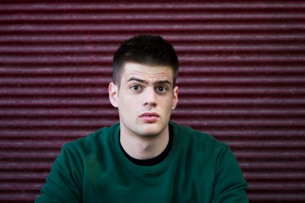 Verwarde jonge man in een groen shirt Gratis Foto