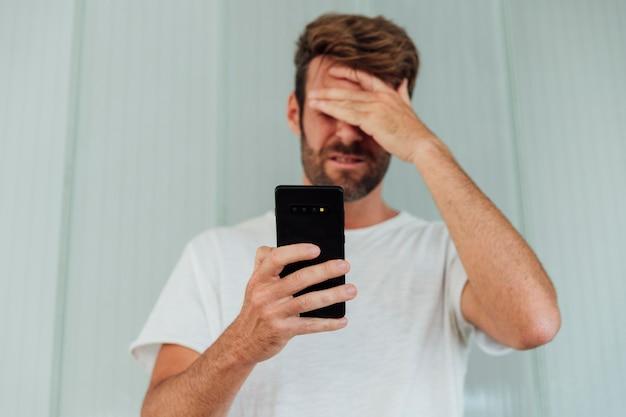 Verwarde man met moderne telefoon Gratis Foto