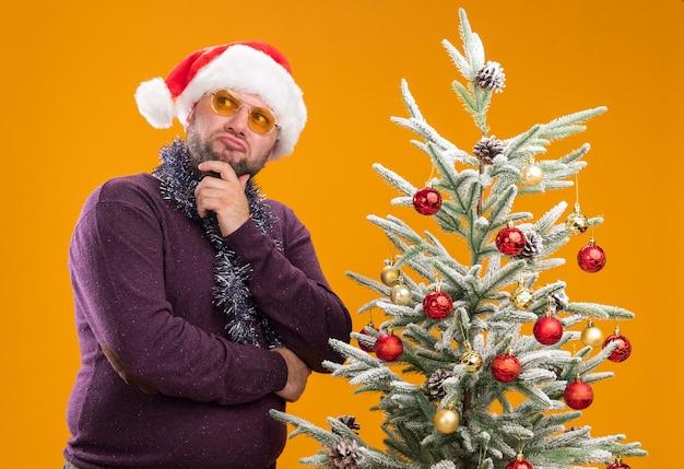 Verwarde man van middelbare leeftijd met kerstmuts en klatergoud slinger rond de nek met glazen staande in de buurt van versierde kerstboom Gratis Foto