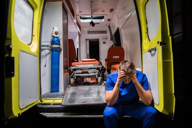 Verwarde paramedicus in een blauw uniform achter in een ambulance-auto Premium Foto