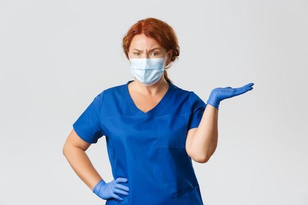 Verwarde sceptische vrouwelijke arts, tandarts in scrubs, gezichtsmasker en handschoenen, schouderophalend, naar rechts wijzend en fronsen teleurgesteld Gratis Foto
