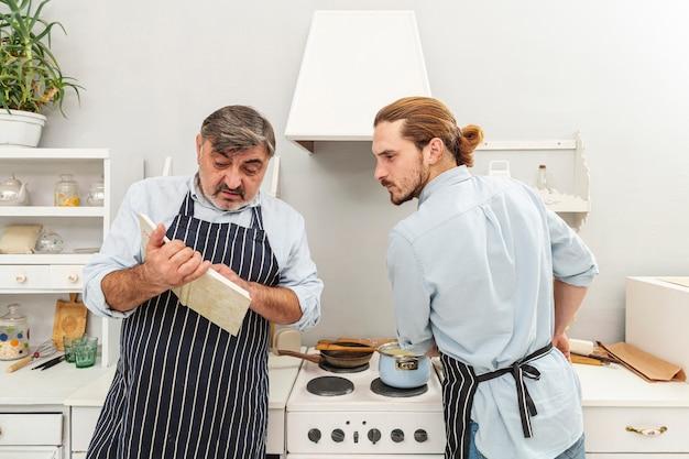 Verwarde vader en zoon die in een kookboek kijken Gratis Foto