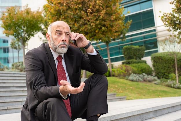 Verwarde volwassen bedrijfsleider die op cel spreekt Gratis Foto