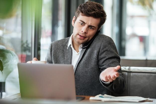 Verwarde zakenmanzitting door de lijst in koffie met laptop computer terwijl het spreken door smartphone Gratis Foto