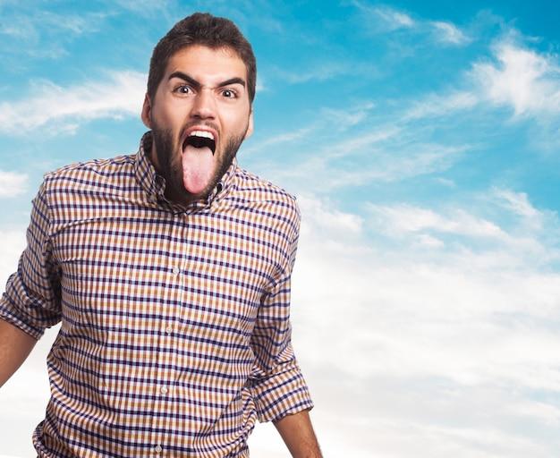 Verwarmde man steekt zijn tong uit Gratis Foto