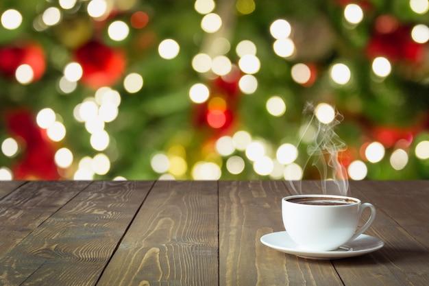 Verwarmende kop van zwarte koffie op houten tafelblad. vage kerstboom als achtergrond. kersttijd. Premium Foto