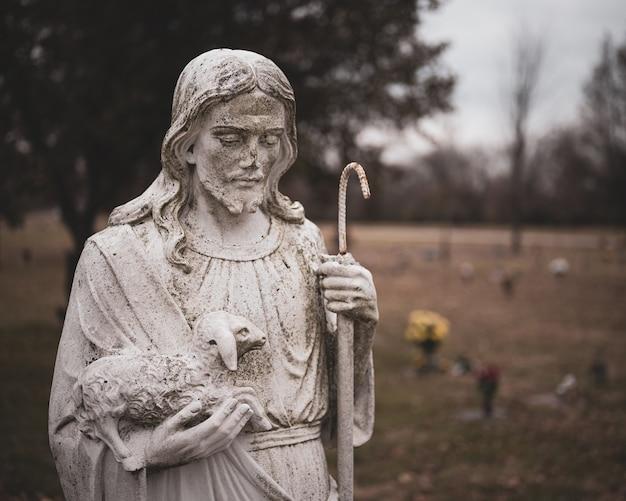Verweerde standbeeld van jezus christus met een schaap in zijn handen op een onscherpe achtergrond Gratis Foto