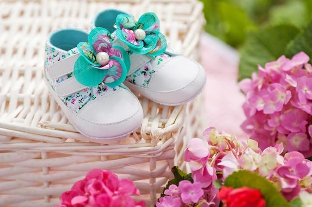 Verzameling van babymeisjesschoenen. buiten met bloemen Premium Foto