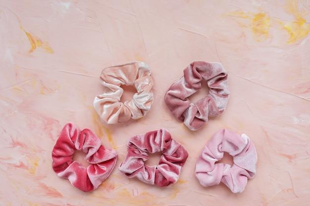 Verzameling van trendy fluwelen scrunchies op roze, plat leggen Premium Foto