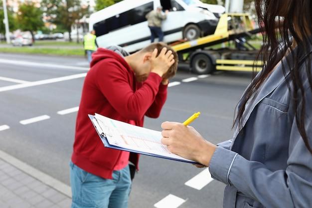 Verzekeringsagent vult verzekering in nadat de auto-ongeluk bestuurder naast hem staat en zijn hoofd vasthoudt Premium Foto