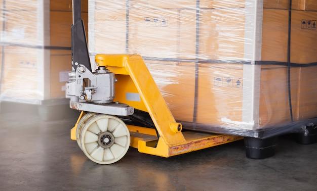 Verzending, vrachtexport en verzendmagazijn. close-up handpallettruck of handpalletkrik met een palletgoederen. Premium Foto
