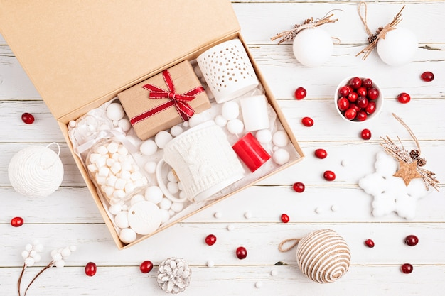 Verzorgingspakket voorbereiden, seizoensgeschenkdoos met marshmalow, kaarsen en beker in rode en witte kleuren. gepersonaliseerde milieuvriendelijke mand voor familie en vrienden voor kerstmis. bovenaanzicht, plat gelegd Premium Foto