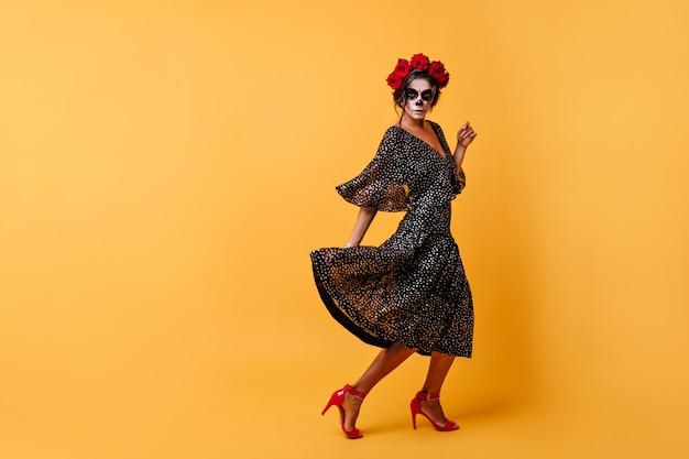 Vet dansend meisje met donker haar gestoken met krans van natuurlijke bloemen op haar hoofd beweegt, poseren met zwarte jurk en zombiemasker Gratis Foto