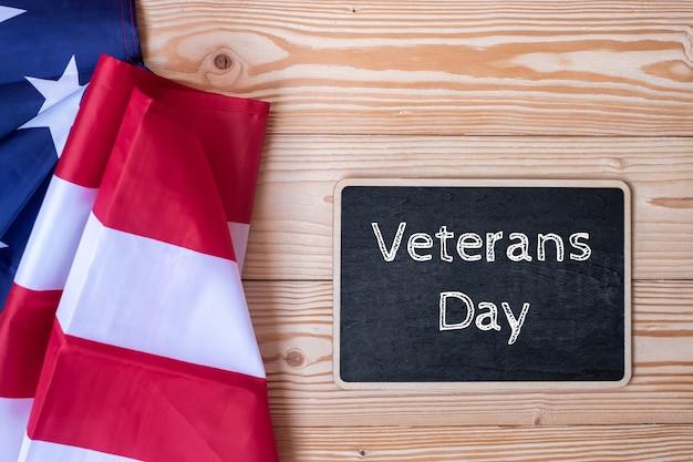 Veterans day-tekst in bord met vlag van de verenigde staten wordt geschreven die Premium Foto