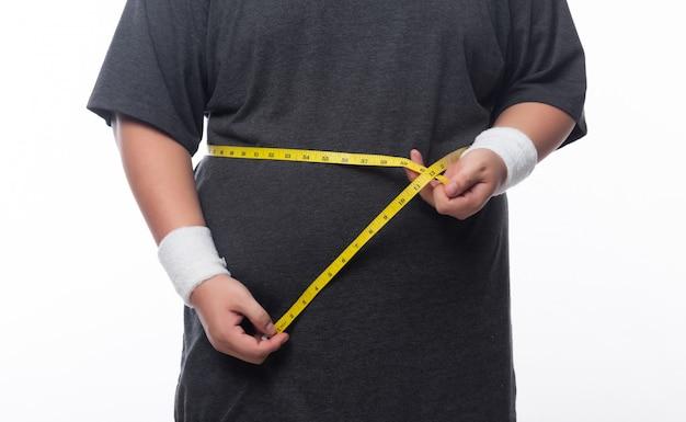Vette mens die een metingsband houdt voor controle zijn lichaam dat op witte achtergrond wordt geïsoleerd Premium Foto