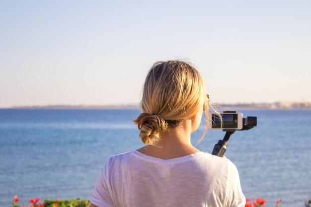 Video blogger meisje. operator met actiecamera op gestabiliseerde grip met cardanische ophanging. Premium Foto