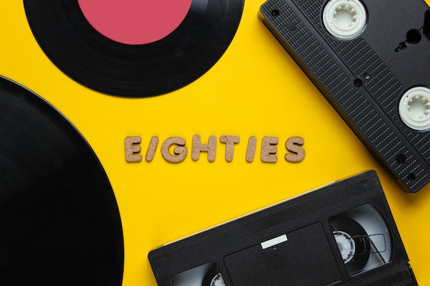 Videocassette en vinylverslagen die op geel worden geïsoleerd Premium Foto
