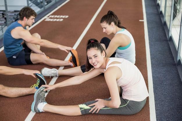 Vier atletische vrouwen en mannen die zich uitstrekt over de atletiekbaan Premium Foto