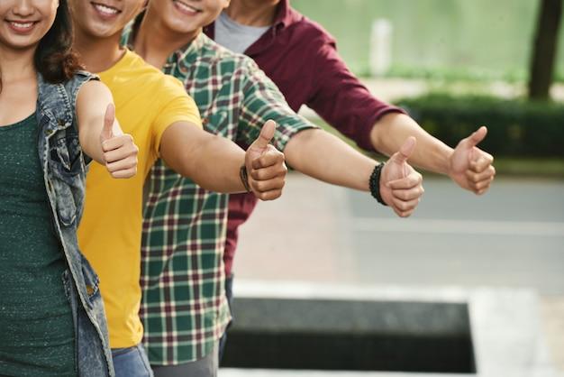 Vier bebouwde jongeren die op een rij tonen beduimelt omhoog gebaar en gelukkig glimlachen Gratis Foto