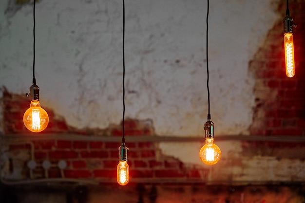 Vier brandende lampen in verschillende vormen die aan lange zwarte draden hangen Premium Foto