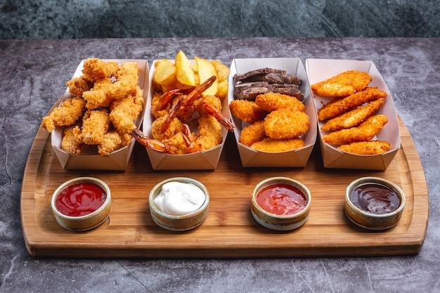 Vier dozen nuggets met kipgarnalen en vis met saus vier Gratis Foto