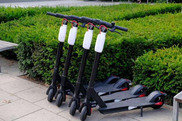 Vier elektrische scooters geparkeerd op een rij op stadsstoep. Premium Foto