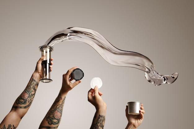Vier getatoeëerde handen met aeropress en reserveonderdelen met water dat uit aeropress vliegt op wit alternatieve koffie brouwen commerciële Gratis Foto